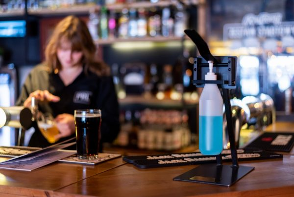 Pump action hand sanitiser for bar use